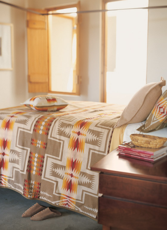 A bed made up with a Pendleton harding blanket.