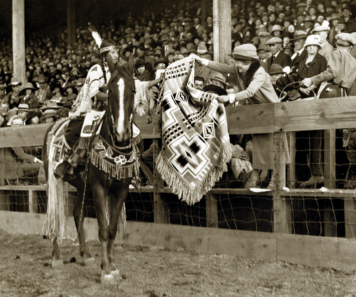 A young Native American woman accepts the gift of a fringed Pendleton shawl in the Harding pattern from a woman in the stands at the Pendleton Round-Up, circa 1920s