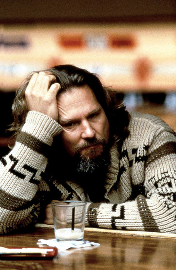 "Jeff Bridges as Jeff Lebowski, AKA ""The Dude,"" sits at the bolwing alley bar with a white Russian in front of him."