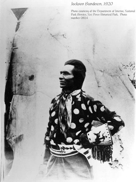 Jackson SUndown poses in front of his family teepee, wearing a dark cotton shirt with large light polkadots, no hat, a beaded belt, and beaded gloves that show a rider on a bucking horse.