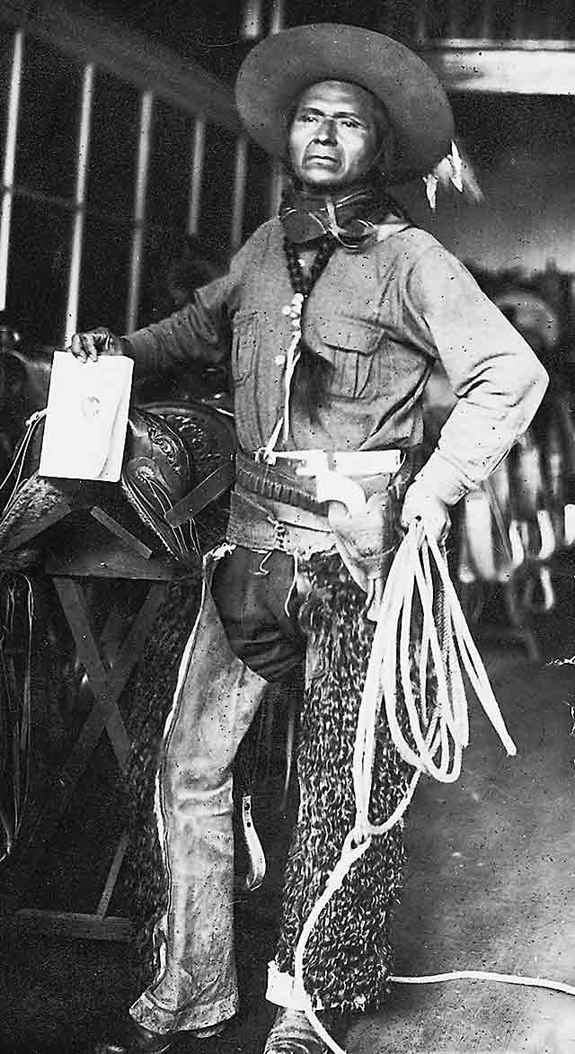 Jackson Sundown poses inside a stable with his championship saddle. He is wearing furry chaps, his signature hat, and a senim workshirt. When he rode, Sundown often tied his braids together on his chest, and they are so tied in this photo. He also holds a lariat.