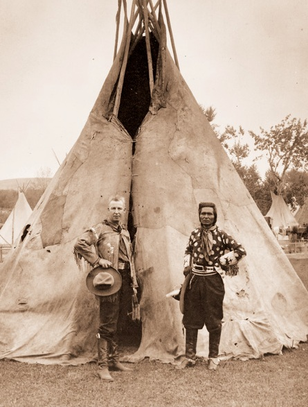Roy Bishop and Jackson Sundown stand in front of a teepee.