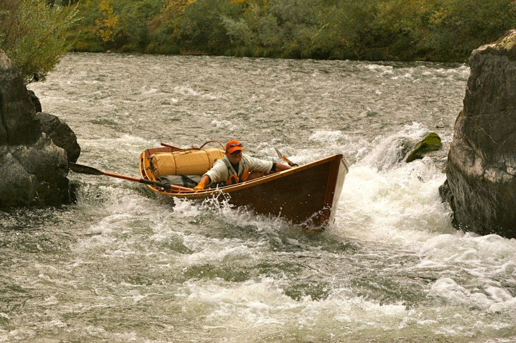 Greg Hatten steers his wooden boat in the rapids of the Rogue River