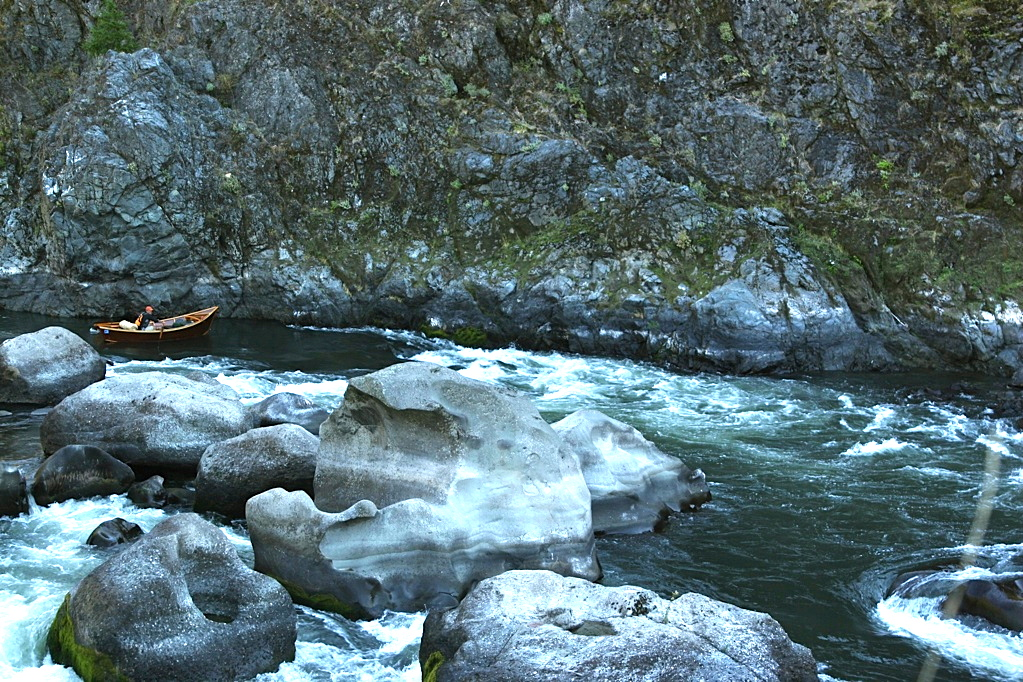 A narrow path around jutting rocks in the Rogue River