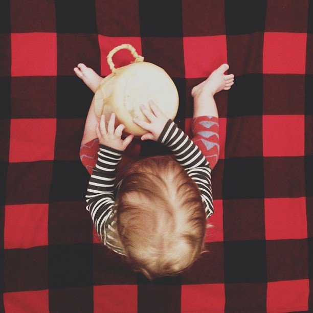 A baby sits on a pendleton blanket, playing the bongos