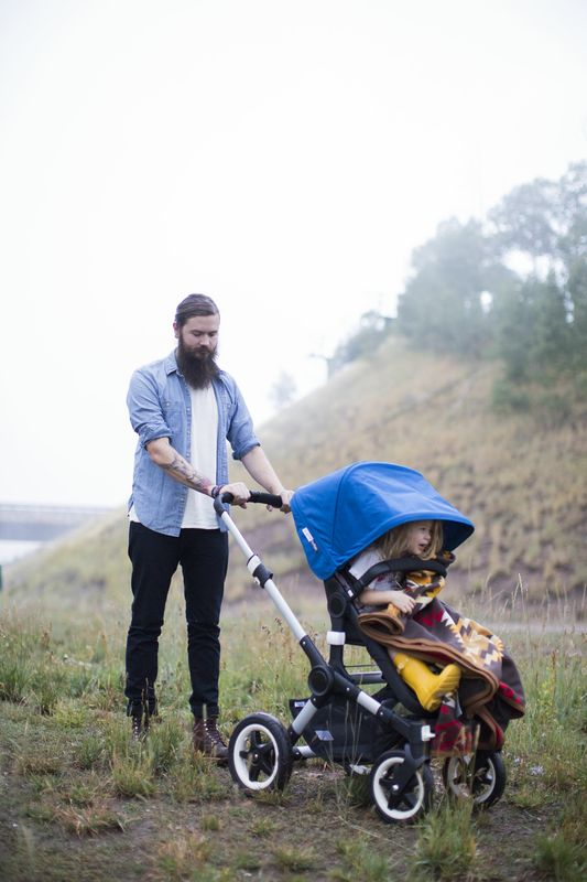 A father pushes a child in a Bugaboo x Pendleton stroller. The child is warming up under a pendleton blanket.
