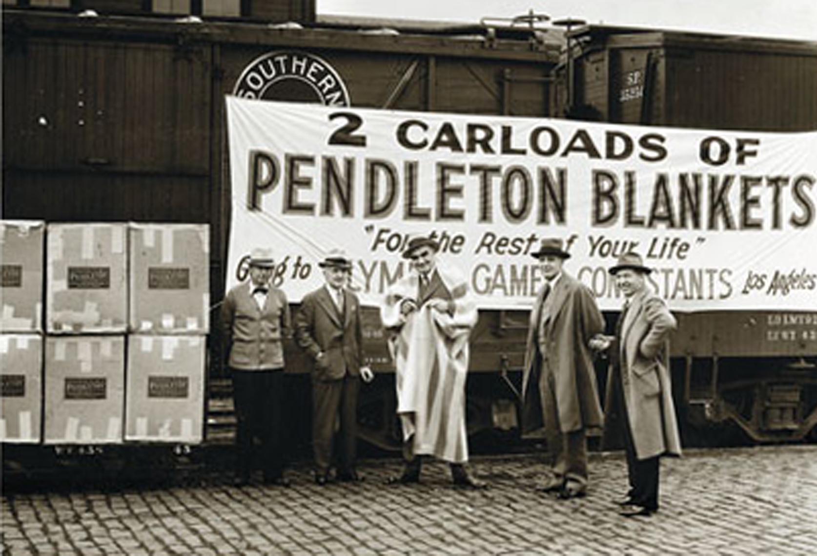 """Five men stand in front of a railroad car that bears the banner, """"2 Carloads of Pendleton Blankets """"For the rest of your life"""" going to Olympic Games Contestants Los Angeles"""""""