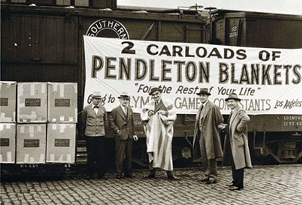 """A photo from the Pendleton archives, of five men waiting beside a train car that has a banner reading """"2 carloads of Pendleton blankets - for the rest of your life - going to the Olympic game Contestants, Los Angeles"""""""