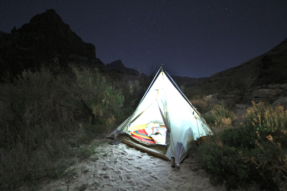 1_Nate_Pickens A tent, lit from within, with Pendleton blankets.