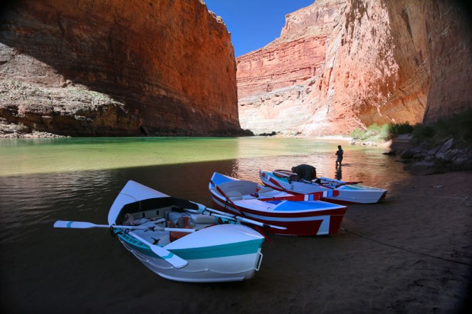 Three beautiful wooden drift boats want in the shallows next to the Colorado RIver, in the shadow of the walls of the Grand Canyon.