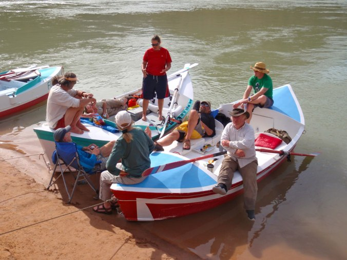Greg Hatten and five friends relax on and around two wooden boats on the banks of the Colorado River.