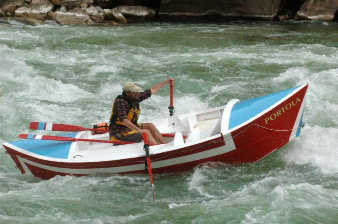 "Greg Hatten maneuvers his way though churning rapids in his wooden boat, the ""Portola."""