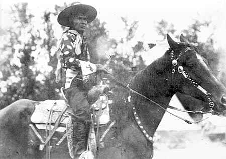Jackson Sundown sits on his horse, wearing his signature hat, a dark cotton shirt with large light polka dots, and beaded gloves.