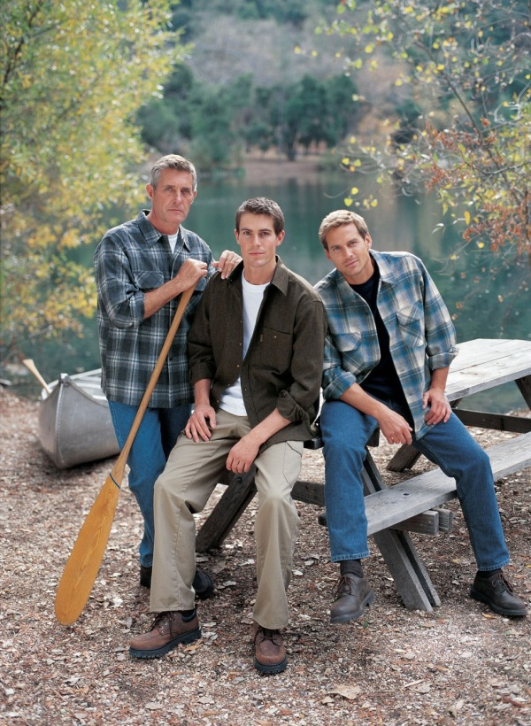 Three men pose near a lake in Pendleton shirts.