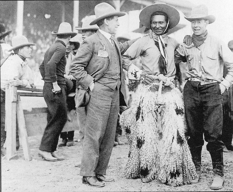 Jackson Sundown poses with another rider to his left and a businessman to his right. Sundown is smiling, and wearing his signature hat and silk kerchiefs, his wooly potted chaps, and beaded gloves that feature a rider on a bucking horse on the cuffs.