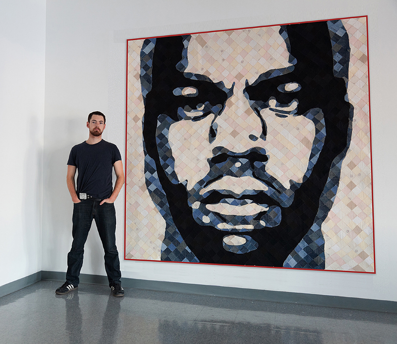 Luke Haynes poses next to one of his quilts.