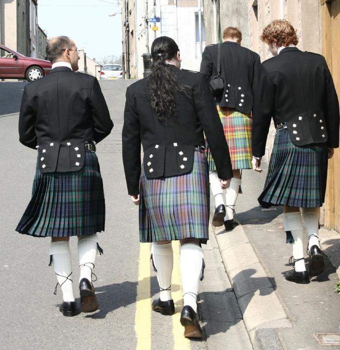 Four men wearing kilts walk down a city street.