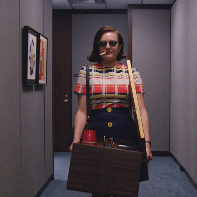 Peggy with a box in her arms, a cigarette in her mouth, wearing a red plaid dress and sunglasses.