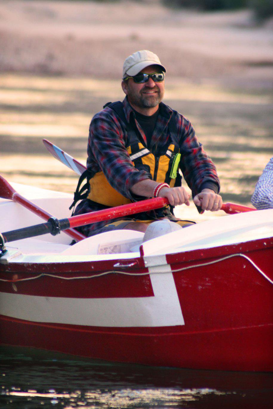Greg hatten in his wooden boat