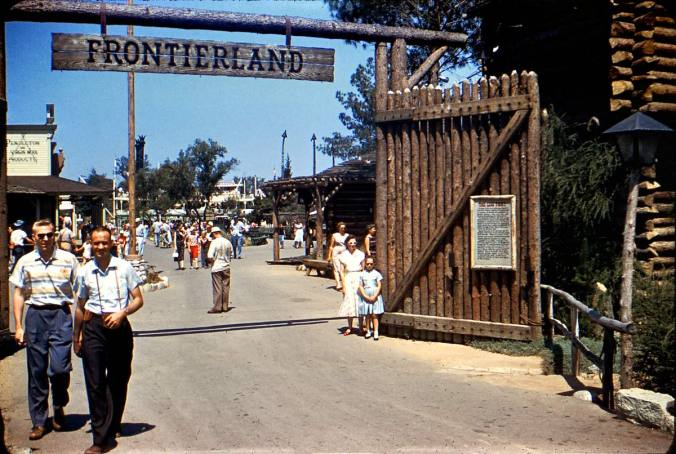 Happy guests at the wooden stockade gate to Frontierland in Disneyland, circa 1960