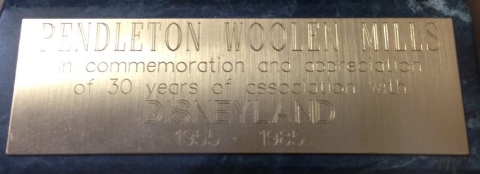 "A closeup of the plaque affixed to the base of the Jiminy Cricket bronze that reads ""Pendleton Woolen Mills in commemoration and appreciation of 30 eyars of association with Disneyland 1955 - 1985"""