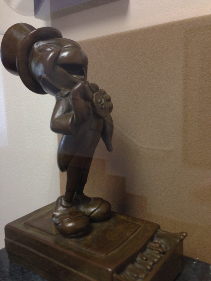 A side view of a small bronze statue of Jiminy Cricket, gifted to Pendleton by Walt Disney.