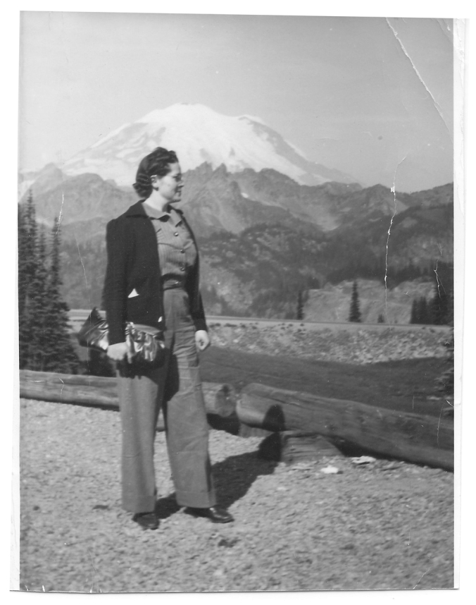A vintage photo of Louise Kelly standing in front of Mt. Rainier.