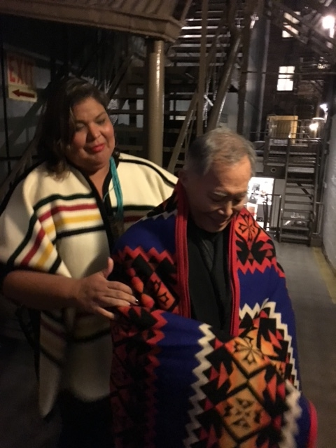 A fan wraps George Takei in a Pendleton blanket after a performace of his Broadway show
