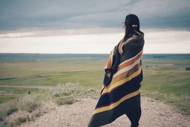 A woman wrapped in a Pendleton blanket looks out on the prairie