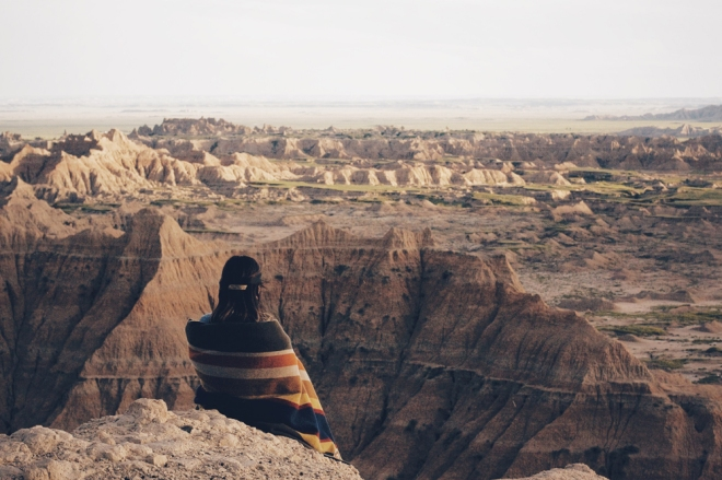 Woman wrapped in blanket looks out into a crevasse in the Badlands