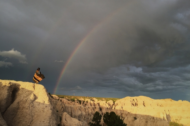 a woman on a bluff, a rainbow in the sky