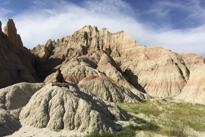 A woman sits on a Pendleton blanket on one of the eroded rock formations of the Badlands