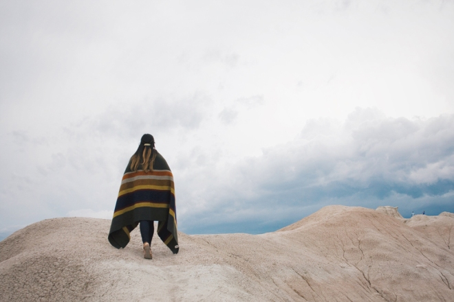 a woman wrapped in a blanket walks on a rock formation