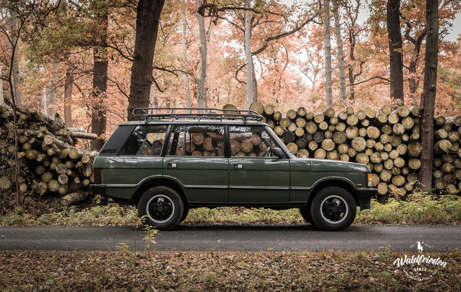 A vintage Range Rover parked by a woodpile