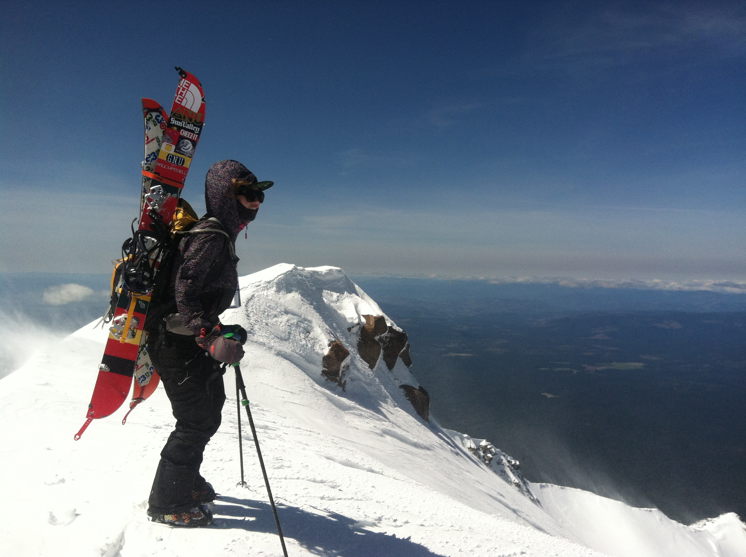 A professional women's snowboarder at the peak of Mount Rainier.