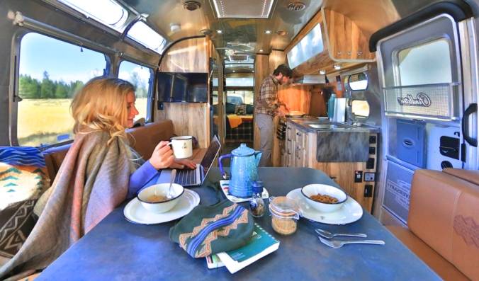 A woman sitting at a table in the Pendleton Airstream