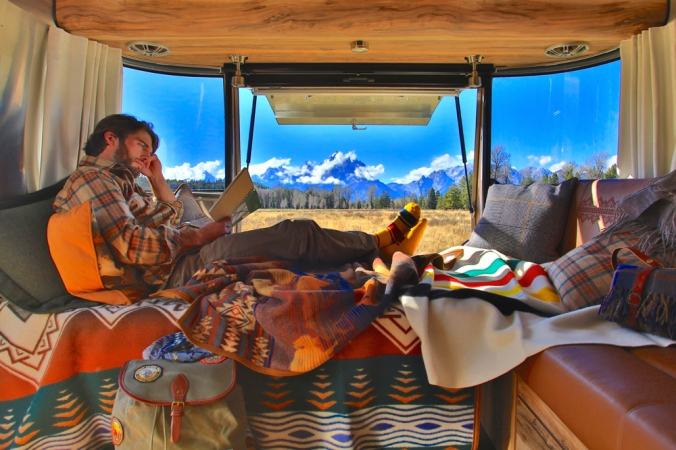 A man sits on the banquette of the Pendleton Airstream, surrounded by Pendleton blankts