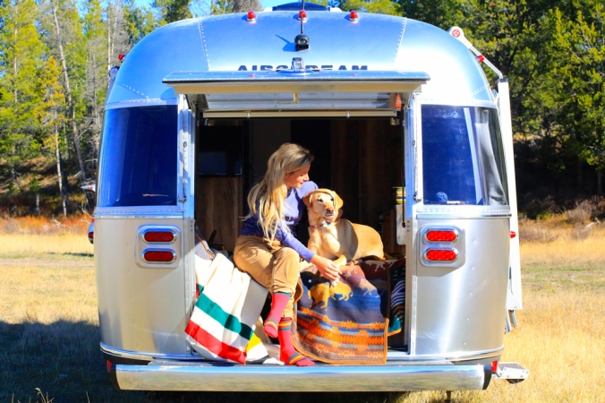A woman and dog sit at the back hatch of the Pendleton Airstream