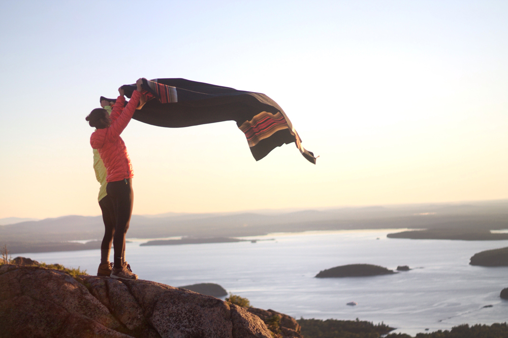Karlov- A woman shakes out a blanket at the coastline of Acadia National Park.