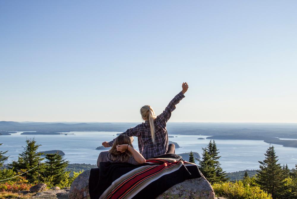 Okoniewski-2 women sit on a boulder with the Pendleton Acadia park blanket.