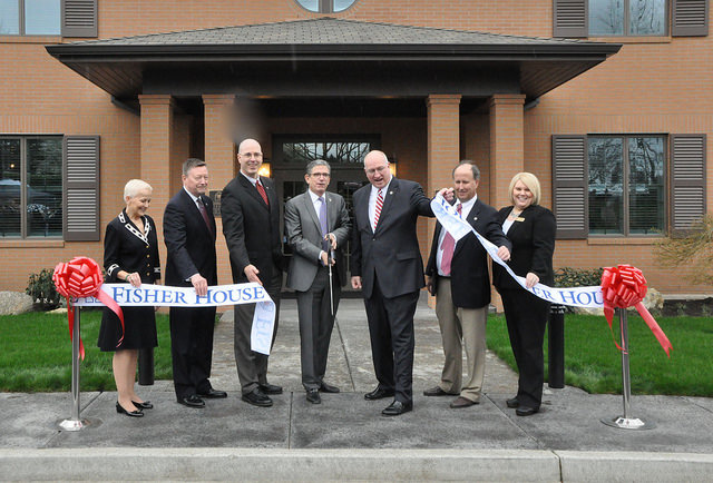 A group of nicely dressed people, inclding representatives of the Fisher House Foundation, and John Bishop, CEO of Pendleton WOolen Mills, participate in a ribbon-cutting to open the new Fisher House in Vancouver, Washington.