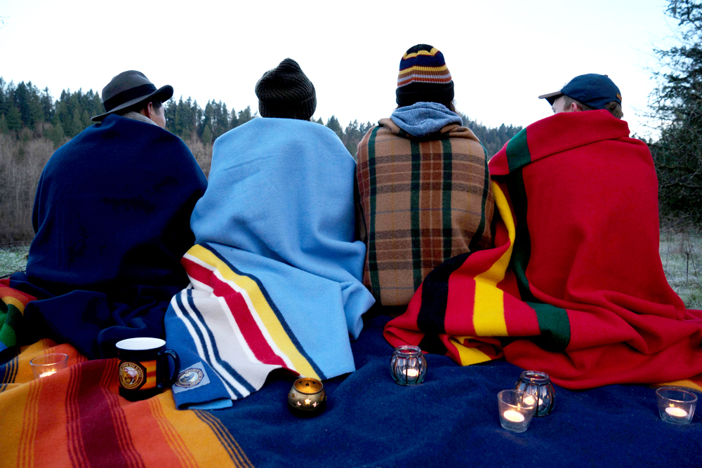 Four people sit side by side, all wrapped in different Pendleton blankets