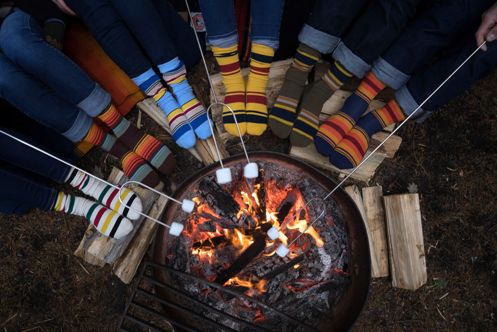 feet wearing National park socks by a campfire, toasting marshmallows