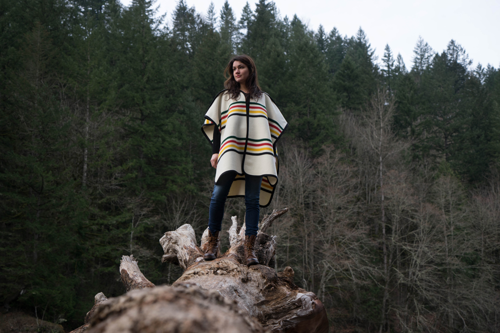 A beautiful woman on a downed tree, wearing a Pendleton cape
