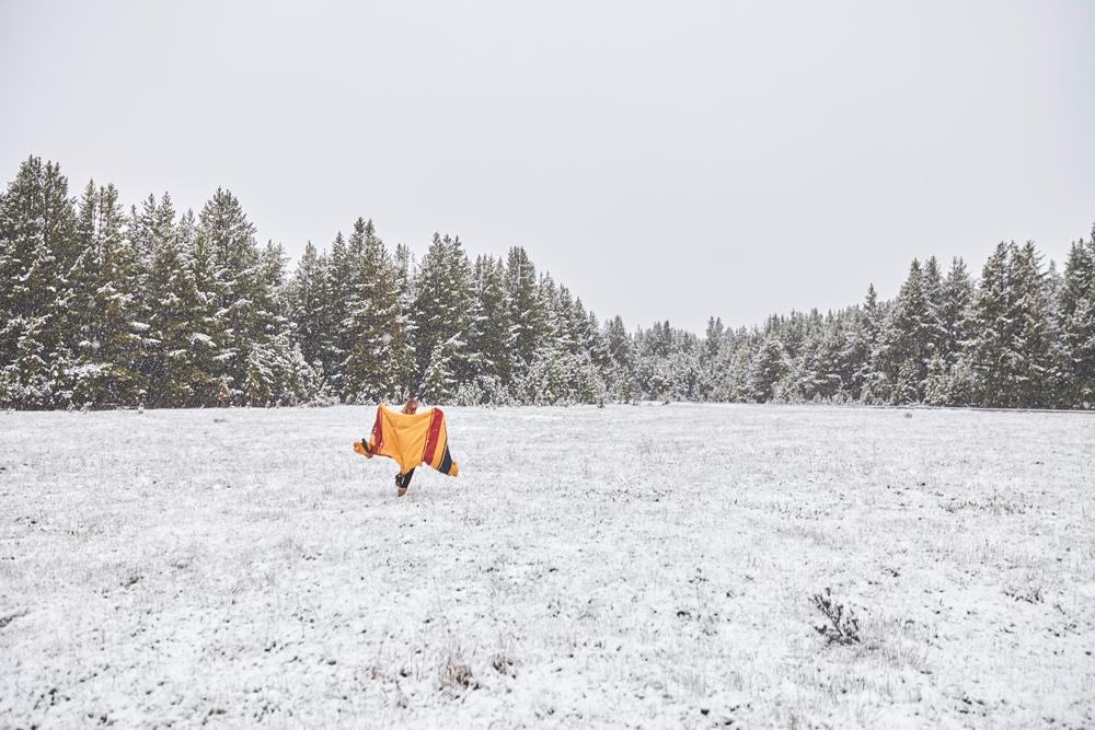 OurFreeWays_ A woman runs across a snowy field