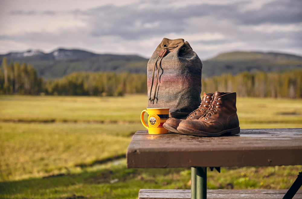 OurFreeWays_ Bag, boots, coffee cup on a picnic table