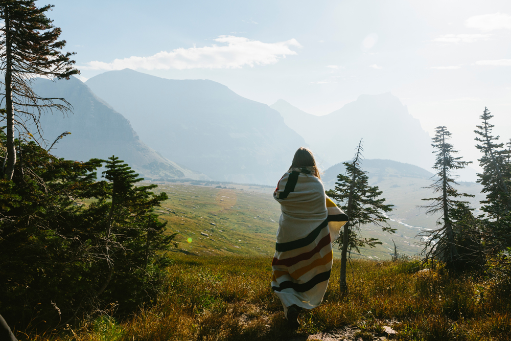 Irey_ A woman wrapped in a Pendleton blanket looks at glaciers in Glacier natioal Park