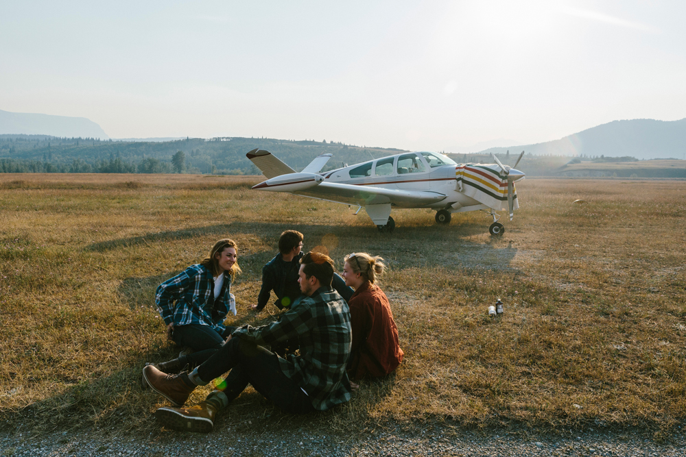 Irey_Four people sit on the ground in front of a small airplane. They are wearing Pendleton wool shirts