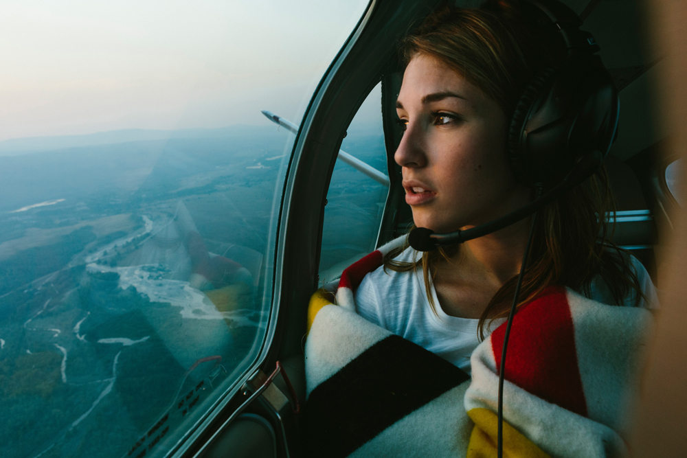 Irey_ A woman looks out the window of a small plane