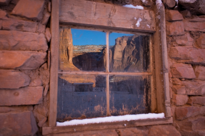 A wondow in a red clay brick home reflects the Canyon de Chelly.